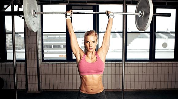 Žena posiluje s těžkou váhou